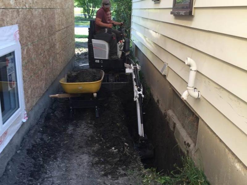 Mini excavator digging for foundation repair