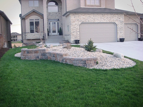 Roman Pisa retaining wall in Autumn Brown. Plants and boulders on berm covered with riverwash.
