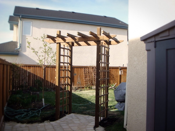 Treated brown arbor leading to back yard.