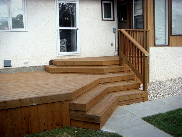 Treated brown deck with large landing and decorative stairs (decks).jpg