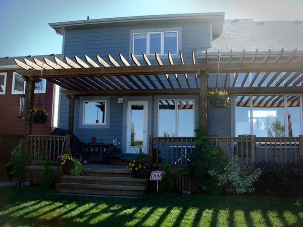 Treated brown rear deck covered with a pergola