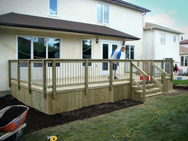 Treated green deck with galvanized pipe rail balusters (decks).jpg
