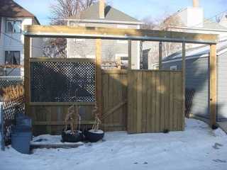 Treated green fence with double sliding door for vehicle access