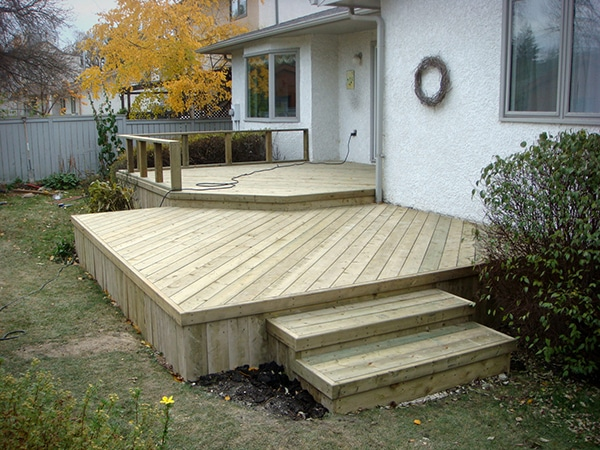 Two-tier treated green deck with custom short railing and diagonal decking.jpg